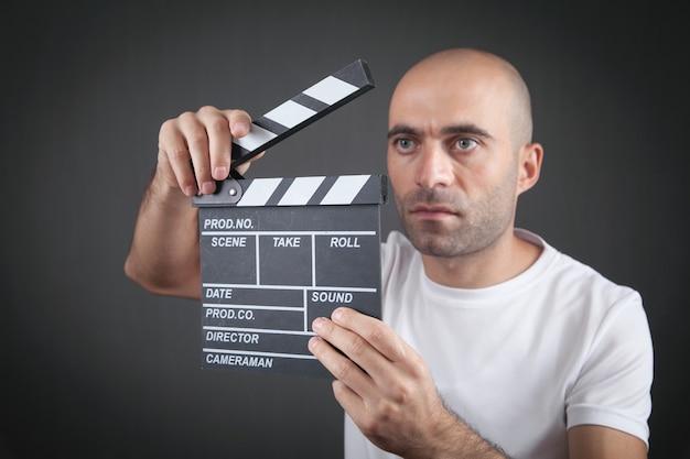 Homem segurando badalo de filme. fazendo filme