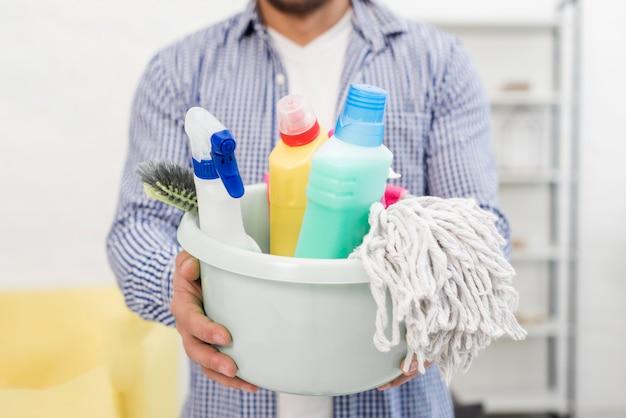Homem segurando balde com produtos de limpeza