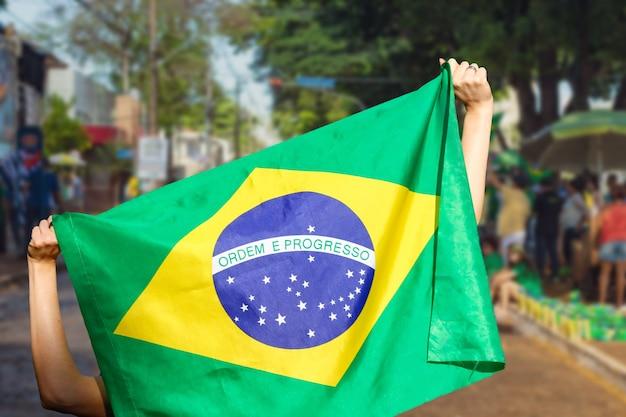 Homem segurando bandeira em manifestação de rua no brasil.