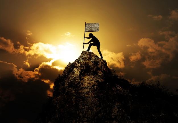 Homem segurando bandeira no pico da montanha e pôr do sol ao ar livre na natureza
