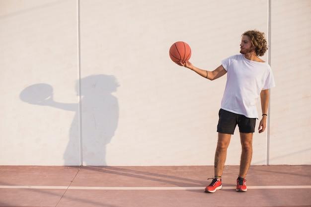 Homem, segurando, basquetebol, frente, parede
