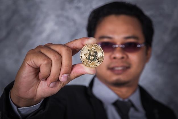 Homem segurando bitcoin dourado na mão