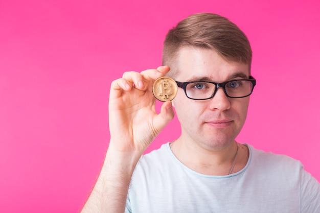 Homem segurando bitcoin em fundo rosa
