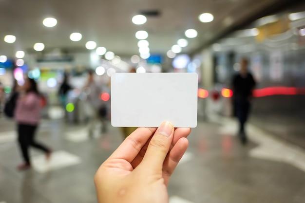 Homem, segurando, branca, cartão negócio, ligado, parede concreta, fundo