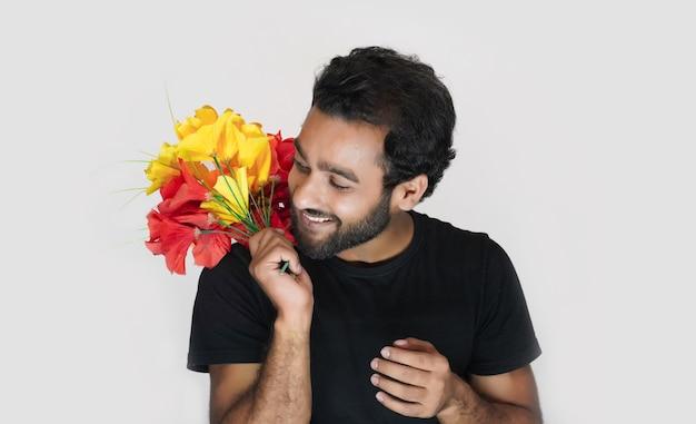 Homem segurando buquê de flores em fundo branco