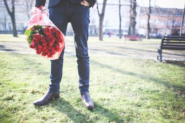 Homem segurando buquê de rosas