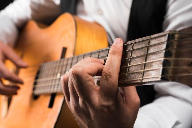 Homem segurando c acorde de barra maior na guitarra