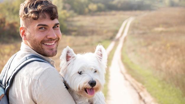 Homem segurando cachorro fofo, tiro médio