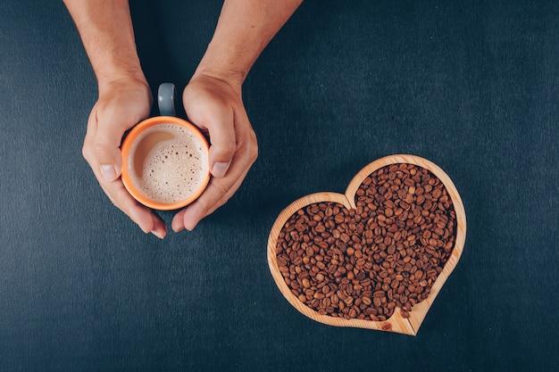Homem segurando café com grãos de café em uma tigela em forma de coração no preto
