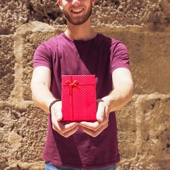 Homem, segurando, caixa presente vermelha, novamente, parede