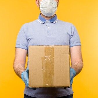 Homem segurando caixas de papelão em máscara e luvas médicas de borracha.