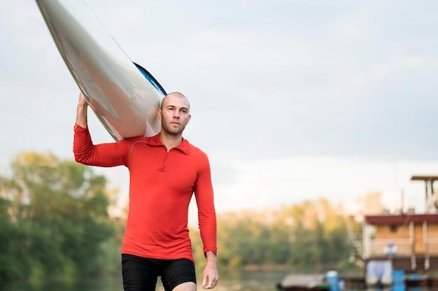 Homem segurando canoa no ombro