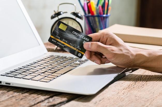 Homem segurando cartão de crédito com laptop