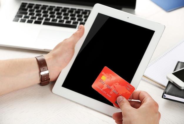 Homem segurando cartão de crédito e tablet no fundo do local de trabalho