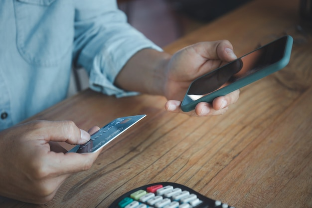 Homem segurando cartão de crédito e telefone inteligente com máquina de pagamento na mesa