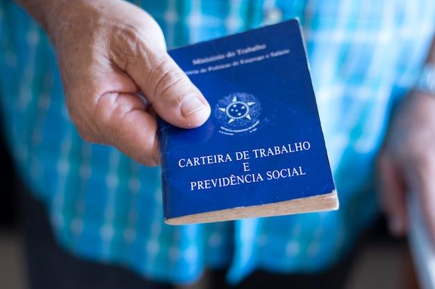 Homem segurando carteira de trabalho brasileira