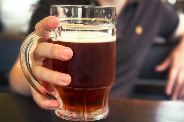 Homem segurando cerveja preta