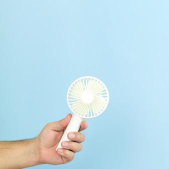 Homem segurando close-up pequeno ventilador usb portátil isolado sobre fundo azul. espaço para texto
