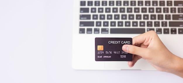 Homem segurando com um cartão de crédito simulado