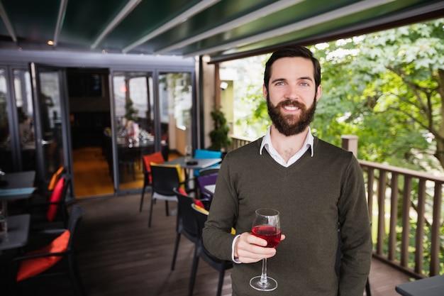 Homem segurando copo de vinho em bar