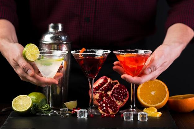Homem segurando copos de cocktail coloridos