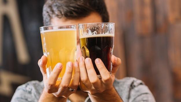 Homem, segurando, copos, de, rum, e, cerveja, frente, seu, rosto