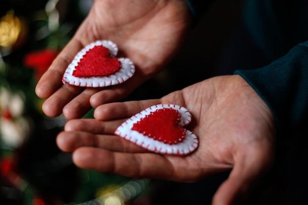 Homem segurando corações de feltro vermelhos nas mãos