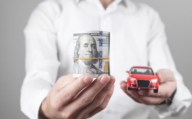Homem segurando dinheiro e carro vermelho de brinquedo.