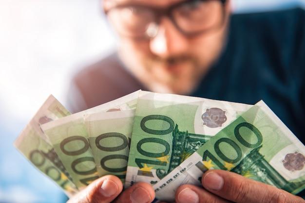 Homem segurando dinheiro europeu