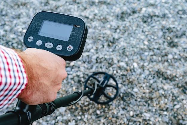 Homem segurando dispositivo detector de metal acima do solo
