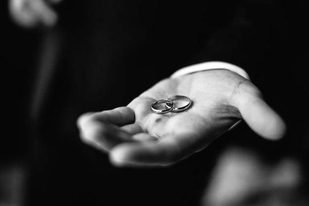 Homem segurando dois anéis de casamento na mão