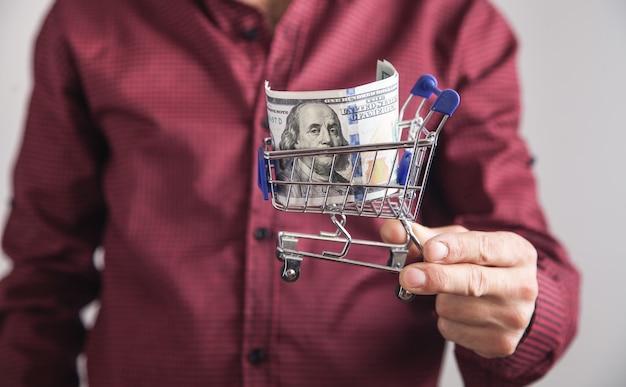 Homem segurando dólares com um carrinho de compras. compras