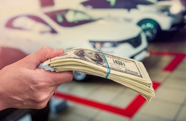 Homem segurando dólares para alugar ou comprar um carro como pano de fundo. conceito de negócios