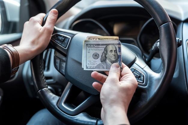 Homem segurando dólares sentado no carro. comprar ou alugar, subornar