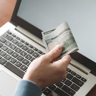 Homem segurando dólares, tecnologias da internet, desenvolvimento de software, aplicativos, programação, ganhos
