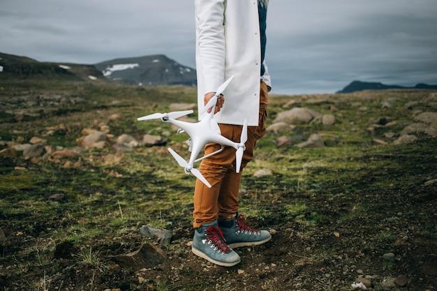 Homem segurando drone e controle remoto na islândia