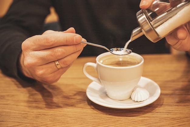 Homem segurando e derramando açúcar do recipiente no café