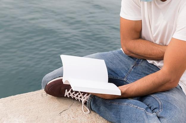 Homem segurando e lendo livro ao ar livre