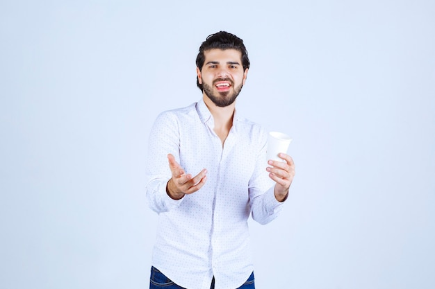 Homem segurando e promovendo uma xícara de café ou café