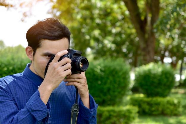 Homem, segurando, e, usando, câmera dslr, e, sentando, sob, árvore, em, parque público, ligado, manhã