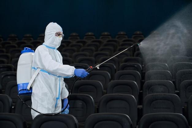 Homem segurando equipamento especial de desinfecção no cinema