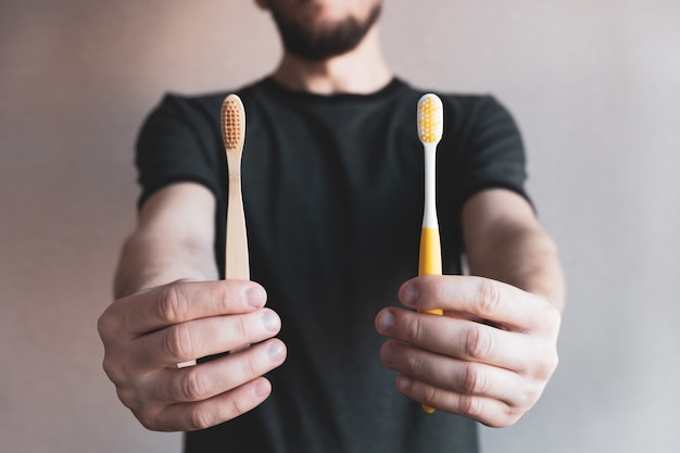Homem segurando escovas de dentes