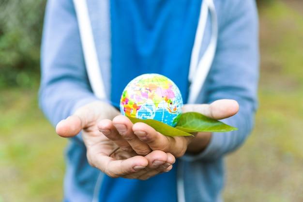 Homem, segurando, esfera, em, palma, de, mão, com, folha