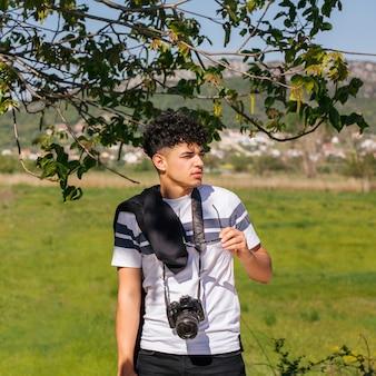 Homem, segurando, espetáculo, com, câmera, ao redor, seu, pescoço, olhando