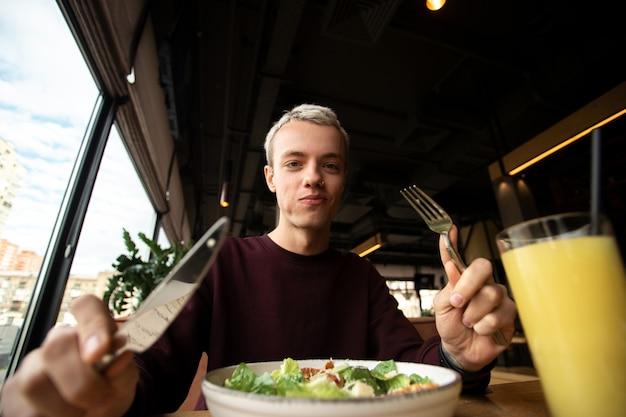 Homem segurando faca e garfo enquanto desfruta de uma comida deliciosa. conceito de autocuidado.