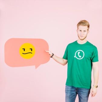 Homem, segurando, fala, bolha, com, infeliz, emoticon