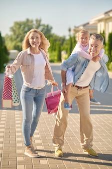 Homem segurando filha nas costas e mulher com compras