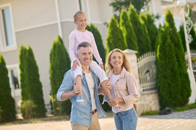 Homem segurando filha nos ombros e esposa