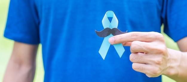 Homem segurando fita azul com bigode para apoiar movember