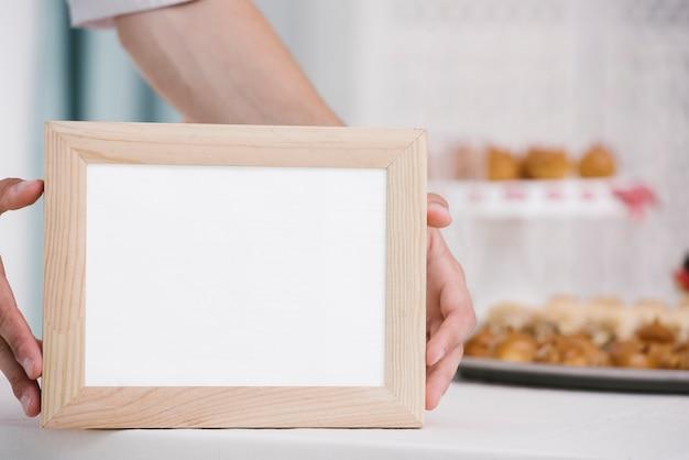 Homem, segurando, frame madeira, com, mock-up